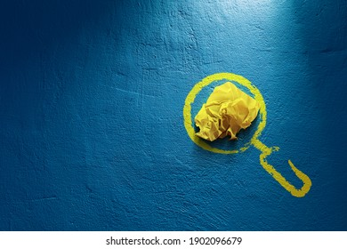 Searching idea concept. Symbol of magnifying glass and crumpled yellow paper on blue wall.