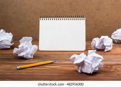Searching an idea, motivation, result, dwaing scetches. White blank notepad book at office worplace crampled paper notes on wooden grunge background. Copy space for ad text