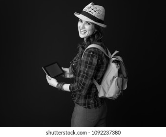Searching for inspiring places. happy active tourist woman in a plaid shirt using tablet PC against background
