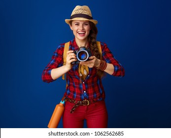 Searching for inspiring places. happy healthy traveller woman in a plaid shirt with modern DSLR camera isolated on blue background