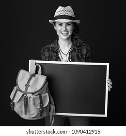 Searching for inspiring places. happy young woman hiker in a plaid shirt showing blank board on background