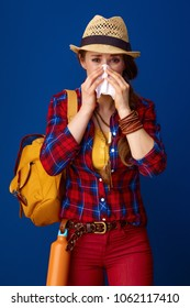 Searching for inspiring places. ill woman hiker in a plaid shirt blowing nose isolated on blue