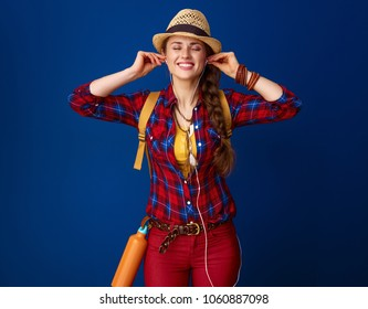 Searching for inspiring places. relaxed adventure woman hiker in a plaid shirt  listening to music on blue background