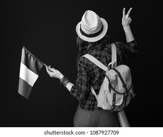 Searching for inspiring places. Seen from behind adventure woman hiker with backpack and the flag of Italy showing victory gesture on background