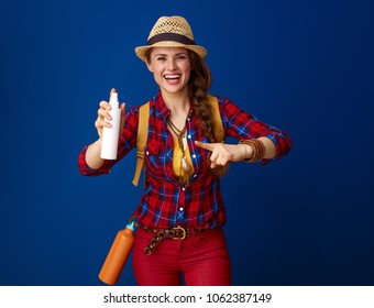 Searching for inspiring places. smiling active tourist woman with backpack pointing at a bottle of spray isolated on blue background