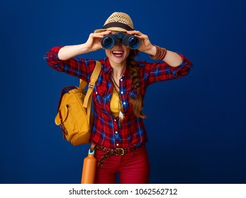 Searching for inspiring places. smiling active tourist woman with backpack looking through binoculars isolated on blue