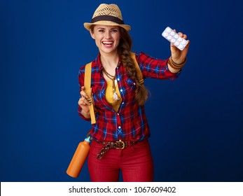 Searching for inspiring places. smiling active woman hiker with backpack showing tablets in a blister pack isolated on blue background
