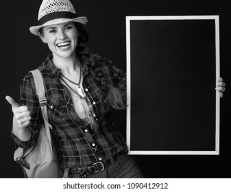 Searching for inspiring places. smiling active woman hiker with backpack showing thumbs up and showing blank board on background