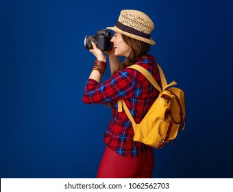 Searching for inspiring places. smiling adventure tourist woman with backpack and DSLR camera taking photo isolated on blue