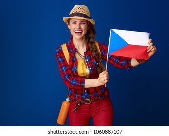 Searching for inspiring places. smiling fit traveller woman with backpack showing the flag of Czech isolated on blue