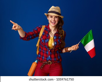 Searching for inspiring places. smiling healthy tourist woman with backpack and the flag of Italy pointing at something against blue background