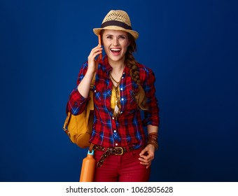 Searching for inspiring places. surprised adventure excited woman hiker in a plaid shirt using a smartphone isolated on blue