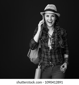 Searching for inspiring places. surprised adventure excited woman hiker in a plaid shirt using a smartphone isolated on