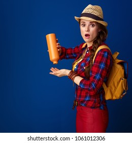 Searching for inspiring places. surprised young tourist woman in a plaid shirt having left no water in bottle isolated on blue background