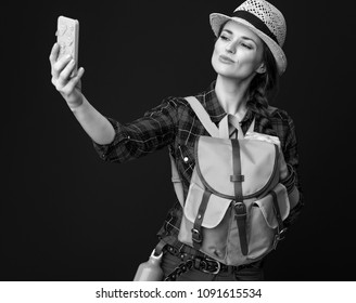 Searching for inspiring places. young traveller woman in a plaid shirt with smartphone taking selfie isolated on background