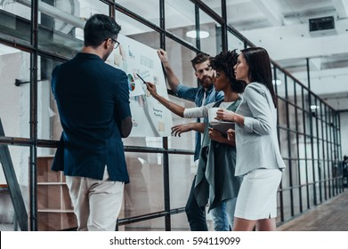 Searching for right decision. Group of confident people planning business strategy while young woman pointing at large paper displayed on the glass wall in the office hallway