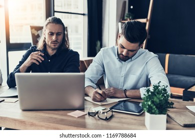 Searching for right decision. Two young modern men in smart casual wear working together while sitting in the creative office