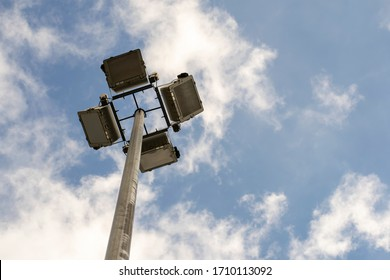 Searchlights on a pole against a blue sky with clouds.
