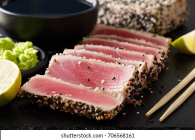 Seared ahi tuna with sesame seeds and soy sauce, wasabi, lime macro on the table. horizontal