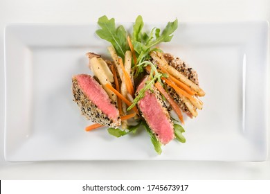 Seared Ahi Tuna slices with sesame crust. Tasty salad made of fish and tossed vegetables.