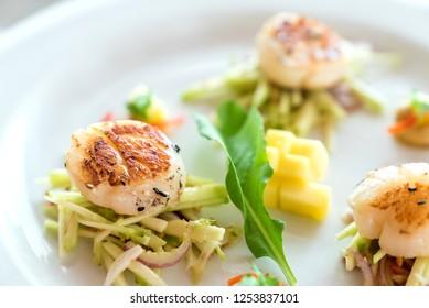 Seared hokkaido scallopes with spicy mango salad on white plate