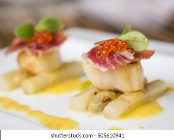 Seared scallops with salmon roe, ham and asparagus on plate