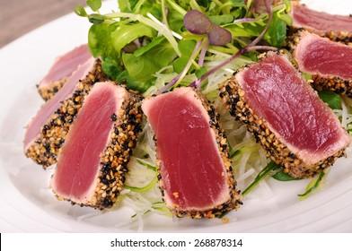Seared tuna coated sesame seeds with green salad on white plate