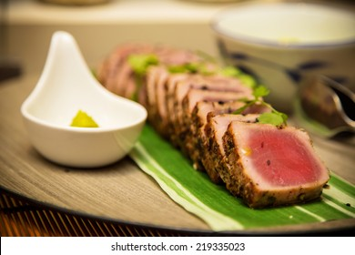 Seared tuna steak called Sashimi traditional Japanese dish with wasabi sauce on side