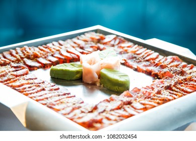 seared yellow fin tuna arranged in tray with wasabi and ginger decoration