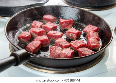 Searing beef bottom round roast cubes in cast iron skillet , meat just added to hot oil , the upper sides are still red