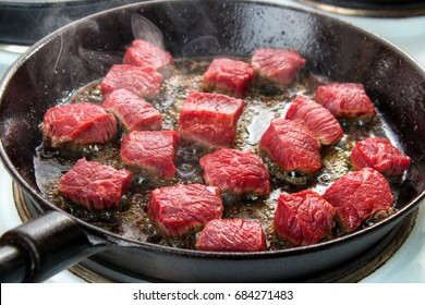 Searing beef bottom round roast cubes in cast iron skillet , closeup
