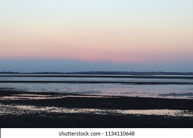 Seasalter Beach at dusk, near Whitstable, Kent - Stony beach at sunset with tide out