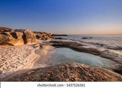 Seascape against the blue sky at sunset. Caspian sea in Kazakhstan. In the foreground-a shell beach, a natural pool in the rocks, white rocks and turquoise clear water. Paradise