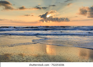Seascape of the Atlantic Ocean as the sun peeks from a cloud and glistens on the Cape Hatteras seashore in the Outer Banks, North Carolina.