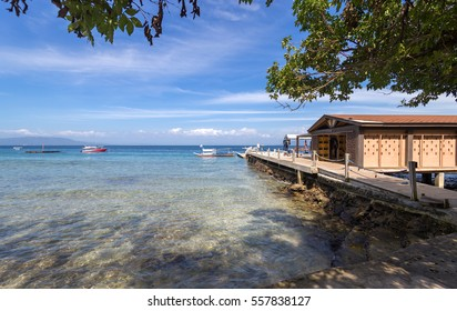 Seascape of beach with transparent sea, blue sky, palms and boats.Taken at Sabang, Puerto Galera, Mindoro island, Philippines, popular tourist and diving spot. Reminds of heaven or travel of dream.