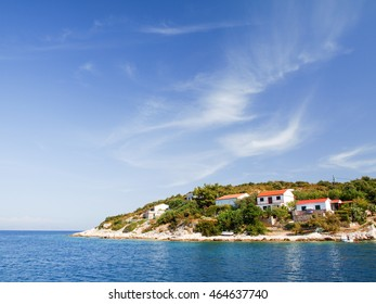 Seascape with beautiful island and with cozy homes, blue sky and sea.