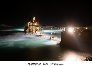 Seascape of Biarritz by night with the Virgin Mary Rock and its bridge. Basque country of France.