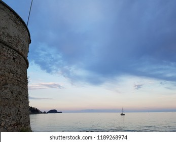 seascape with boat and ancient tower in Alassio, italian riviera