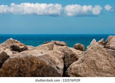 Seascape with breakwater in foreground. Mediterranean Sea and sky with clouds, Italy, Europe