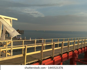 seascape. bridge, berth on the shore, wooden flooring on a metal base, veranda with white curtains, curtains fluttering in the wind, on the shore there are swings floor striped awnings, in the sea flo