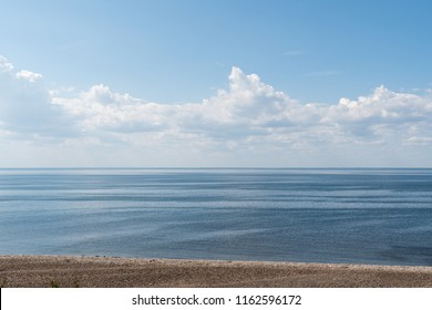 Seascape with calm water and clouds in the sky by the coastline
