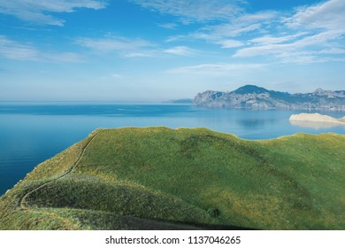 Seascape, cliff with green grass, beautiful mountains in the background