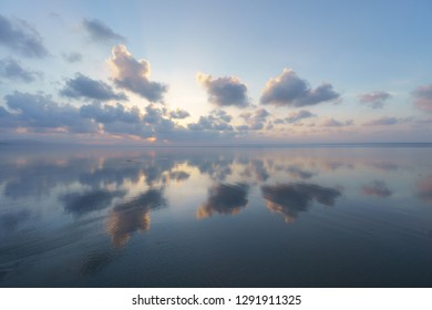 Seascape with clouds reflections on beach