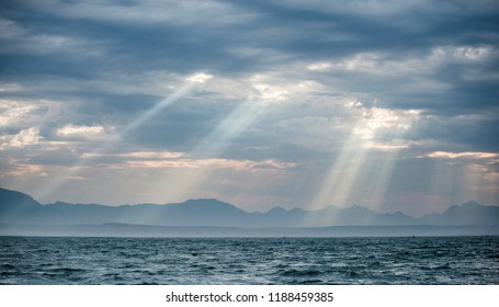 Seascape.  Clouds sky. The rays of the sun through the clouds in the dawn sky,  Silhouettes of Mountains on the Horizon. False bay. South Africa.