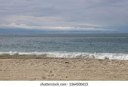 Seascape of a cloudy sky over a sandy beach near the ocean