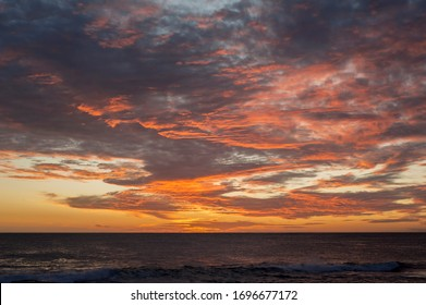 Seascape composition of a sunset, dark grey ocean, low horizon, back lit with bright red and orange clouds after sun  set.   Dark moody sky with pink and orange clouds.