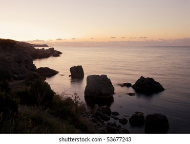 Seascape at dawn with silhouettes of coast rocks
