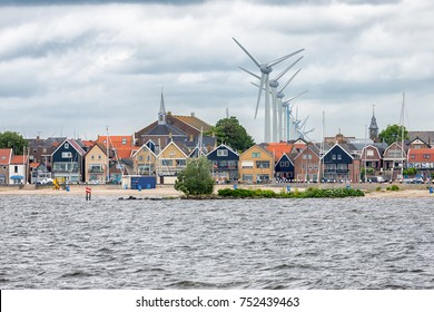 Seascape Dutch fishing village Urk with big wind turbines raising above the skyline of the houses