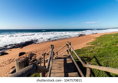 Seascape of empty wooden walkway leading onto rocky beach, waves and sea against blue coastal skyline in South Africa