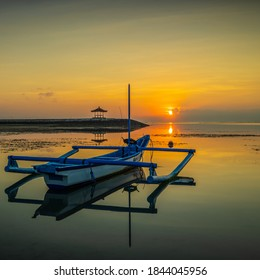 Seascape. Fisherman boat jukung. Sunrise landscape. Gazebos on an artificial island in the ocean. Water reflection. Sun on horizon. Slow shutter speed. Soft focus. Sanur beach, Bali, Indonesia. - Shutterstock ID 1844045956